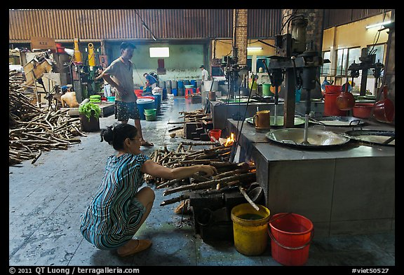 Woman feeding furnace in cococut candy factory. Ben Tre, Vietnam (color)