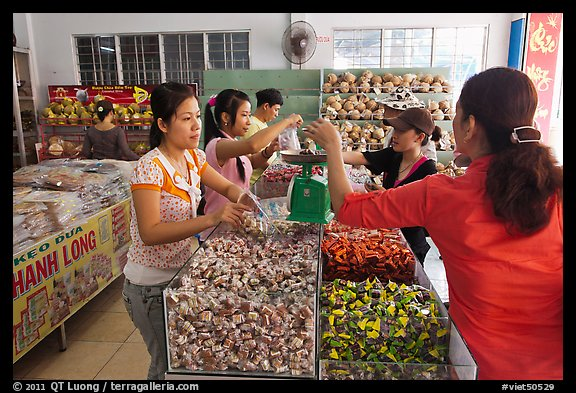 Women weighting coconut candy in retail store. Ben Tre, Vietnam (color)