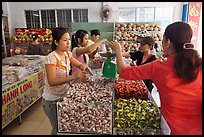 Women weighting coconut candy in retail store. Ben Tre, Vietnam ( color)