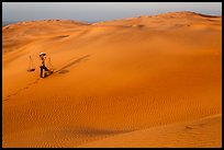 Red sand dunes and woman with carrying pole and baskets. Mui Ne, Vietnam (color)