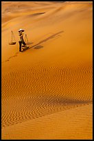 Woman with yoke baskets on sands. Mui Ne, Vietnam ( color)