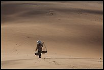 Woman walking on dune field with yoke baskets. Mui Ne, Vietnam ( color)