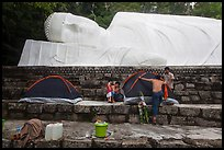 Pilgrims pitch tent below reclining Buddha statue. Ta Cu Mountain, Vietnam (color)