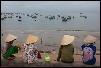 Four women in conical hats watch fishing activity from high above fishing village. Mui Ne, Vietnam ( color)