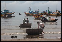 Fishermen on roundboats and fishing fleet. Mui Ne, Vietnam (color)