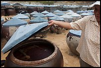 Woman examining vat of fish sauch. Mui Ne, Vietnam ( color)