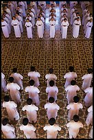 Men and women dressed in white stand in opposing rows in Cao Dai temple. Tay Ninh, Vietnam ( color)
