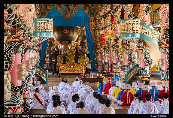 Dignitaries (in colored robes) and other followers praying at the Main hall, Cao Dai temple. Tay Ninh, Vietnam (color)