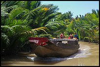Boat navigating narrow waterway, Phoenix Island. My Tho, Vietnam (color)