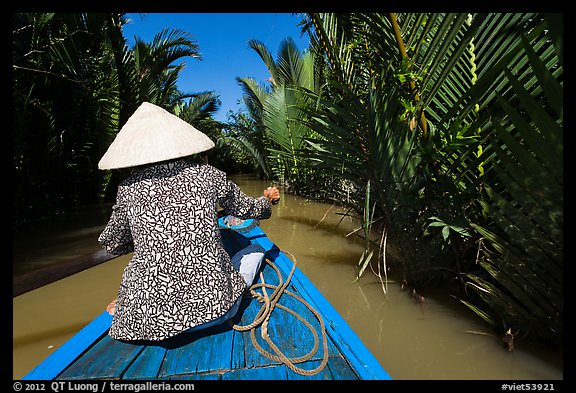 Woman rowing boat in canal lined up with vegetation, Phoenix Island. My Tho, Vietnam (color)