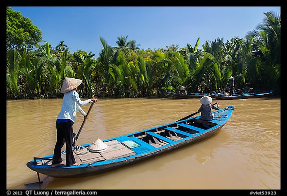 Women row canoes, Phoenix Island. My Tho, Vietnam (color)