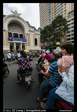 Family on motorbike watching performance at opera house. Ho Chi Minh City, Vietnam (color)