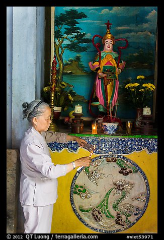 Woman lighting incense at side altar. Da Nang, Vietnam (color)
