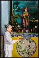 Woman lighting incense at side altar. Da Nang, Vietnam ( color)