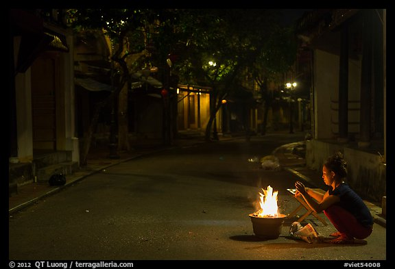 Woman burning paper on street at night. Hoi An, Vietnam (color)