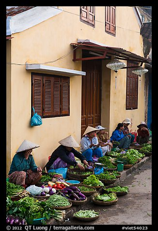 Vegetable vendors sitting in front of old house. Hoi An, Vietnam (color)