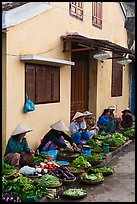 Vegetable vendors sitting in front of old house. Hoi An, Vietnam ( color)
