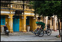 Motorcyle and cyclo in front of old townhouses. Hoi An, Vietnam (color)