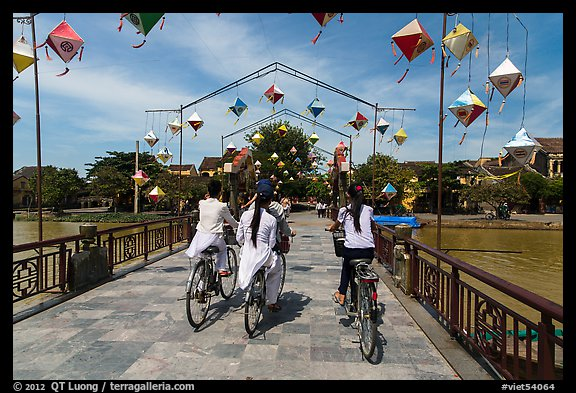 Girls on bicycle cross bridge festoned with lanterns. Hoi An, Vietnam (color)