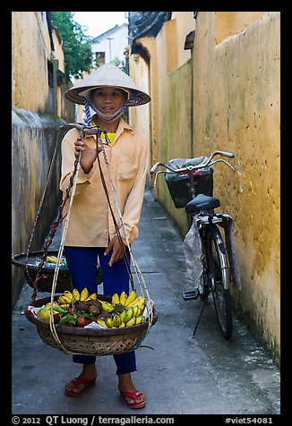 Fruit vendor carrying bananas. Hoi An, Vietnam (color)
