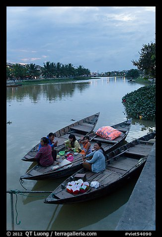 Family having dinner on boats at dusk. Hoi An, Vietnam