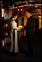 Couple holding candles in front of Japanese bridge at night. Hoi An, Vietnam (color)