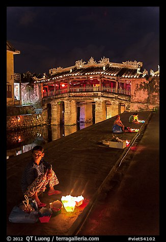 Candle vendors in front of Japanese bridge at night. Hoi An, Vietnam (color)