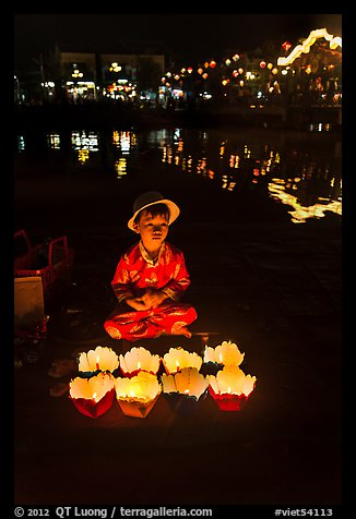 Boy selling candle lanterns by the river. Hoi An, Vietnam (color)