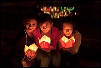 Faces of three women in the glow of candle boxes. Hoi An, Vietnam (color)