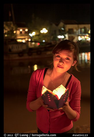 Woman holding candle box at night. Hoi An, Vietnam (color)