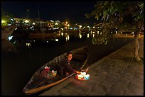 Woman sitting in rowboat selling candles on quay. Hoi An, Vietnam (color)