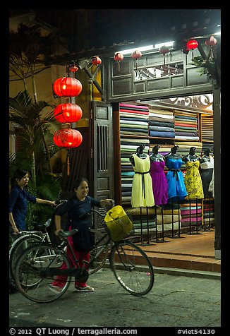 Women with bicycles in front of taylor shop. Hoi An, Vietnam (color)