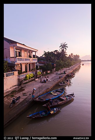 Waterfront and quay with vendors at sunrise. Hoi An, Vietnam (color)