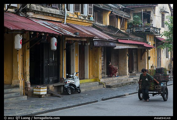 Man pulling cart in front of old townhouses. Hoi An, Vietnam (color)