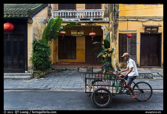 Man riding tricycle cart in front of old townhouses. Hoi An, Vietnam (color)