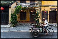 Man riding tricycle cart in front of old townhouses. Hoi An, Vietnam ( color)