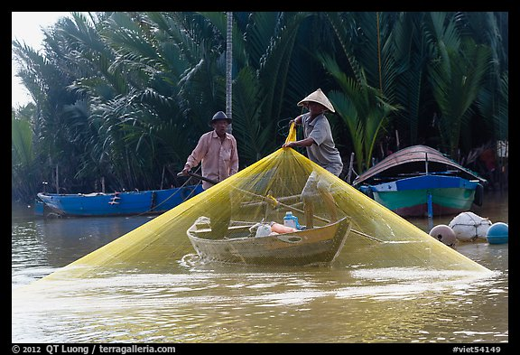 Fisherman pulls up net from rowboat. Hoi An, Vietnam (color)