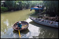Man rows coracle boat in river channel. Hoi An, Vietnam (color)