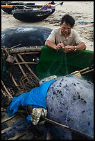 Fisherman repairing net on beach. Da Nang, Vietnam ( color)