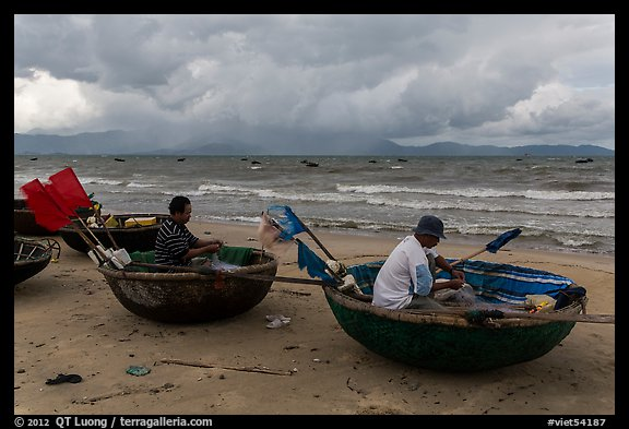 Fishermen mending nets in coracle boats. Da Nang, Vietnam (color)