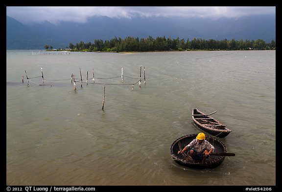 Man rowing coracle boat in lagoon. Vietnam (color)