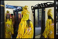 Woman in imperial dress checking herself in mirror, citadel. Hue, Vietnam ( color)