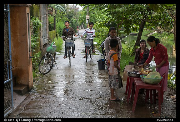 Canalside street with bicyclists and food stand, Thanh Toan. Hue, Vietnam