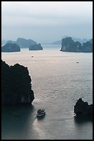 Tour boat navigating between islets. Halong Bay, Vietnam (color)