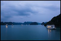 View of bay with lights of anchored tour boats at dawn. Halong Bay, Vietnam (color)