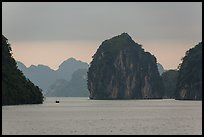 Fishing boat dwarfed by limestone islands. Halong Bay, Vietnam (color)