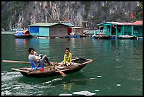 Man holding infant while rowing with feet, Vung Vieng village. Halong Bay, Vietnam ( color)