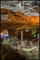 Tourists walking in cavernous chamber, Sungsot cave. Halong Bay, Vietnam (color)