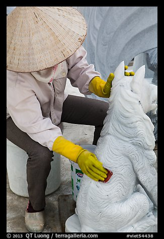 Woman polishing stone carving by hand. Vietnam (color)