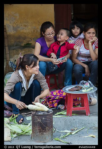 Woman roasting corn in the street. Bat Trang, Vietnam (color)